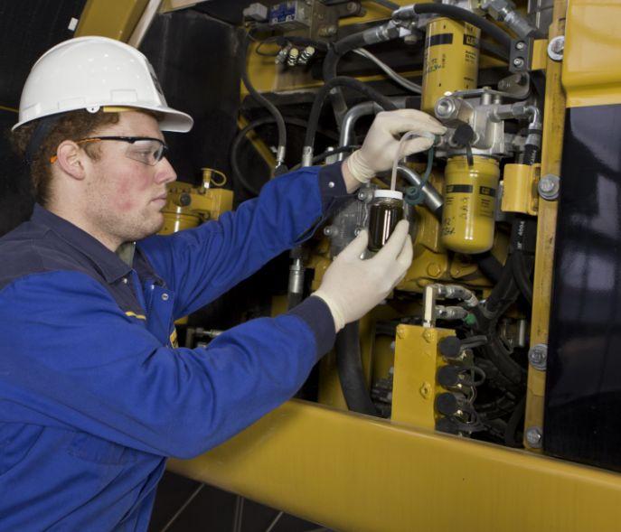 Cat technician taking oil