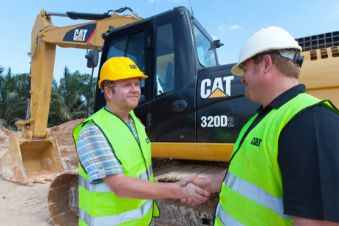 Two man in construction vests shaking hands